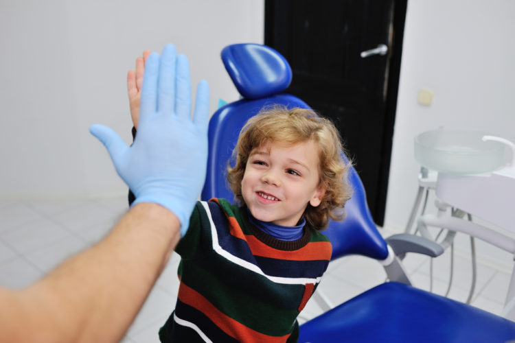 Child high-fiving dentist